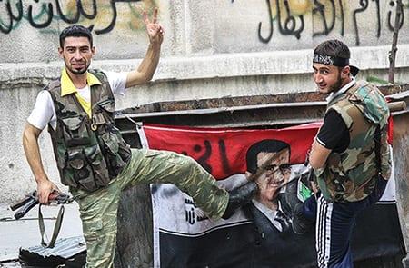Min fiendes fiende är min vän. FSA-soldat och Al-Nusra-medlem sparkar på en Assadflagga. Foto: Flickr/FreedomHouse/CC BY 2.0
